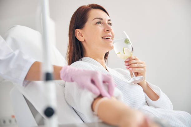 Joyous female patient drinking a healthy beverage during a medical procedure in a beauty clinic